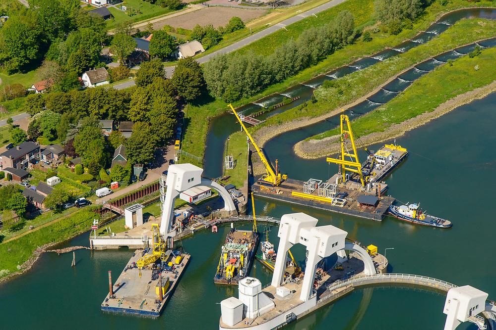 Nederland, Utrecht, Hagestein, 13-05-2019; stuw in de rivier de Lek, dient om het waterpeil in de rivier te reguleren en het scheepvaartverkeer mogelijk te maken. Het gehele stuwcomplex wordt gerenoveerd. Op de foto wordt de zuidelijke vizierschuif vervangen, er is een tijdelijk waterkering geplaatst zodat de nieuwe schuif geïnstalleerd kan worden. Op de dekschuiten de oude en nieuwe schuiven.<br /> Naast de stuw de schutsluis voor de scheepvaart, vissen kunnen gebruik maken van de de vistrap (of vispassage).<br /> Weir in the river Lek, regulates and manages the water level. The Lek is a rain river, with especially in the winter large amounts of water (melt water), in the summer there is a shortage of water, the weir ensures sufficiently high water level for shipping. Next to the dam fish ladder and shipping lock. The complex is being renovated, the visor slides are being replaced.<br /> luchtfoto (toeslag op standard tarieven);<br /> aerial photo (additional fee required);<br /> copyright foto/photo Siebe Swart