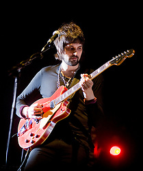 Sergio Pizzorno Kasabian guitarist on stage at the Sheffield Arena during the West Ryder Pauper Lunatic Asylum 23 November 2009