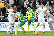 Swansea City captain Ashley Williams (l) tackles Norwich's Steven Naismith (green boots). Barclays Premier league match, Swansea city v Norwich city at the Liberty Stadium in Swansea, South Wales on Saturday 5th March 2016.<br /> pic by  Carl Robertson, Andrew Orchard sports photography.