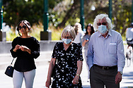 A couple wearing facemasks are seen walking along the Yarra during the 35th day of zero COVID-19 cases in Victoria, Australia. School and community sport is ramping up and as the weather improves, more people are venturing out and about to enjoy this great city. Pressure is mounting on Premier Daniel Andrews to keep his promise of removing all remaining restrictions. (Photo by Dave Hewison/Speed Media)