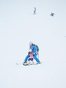 Parent teaching child to ski at resort, Nagano, Japan