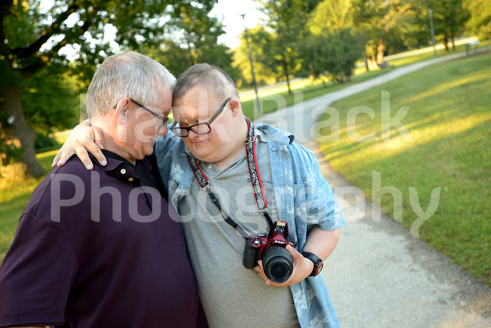 Professional photographer Geoffrey Mikol give his dad Paul a hug while the two were out photographing in the Morton Arboretum.