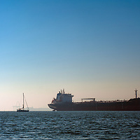 A sailboats passes a container ship anchored in San Francisco Bay, waiting to load cargo at docks in either Oakland or San Francisco.