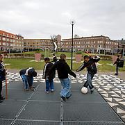 Nederland Rotterdam 8 maart 2008 20080308 .Millinxpark in achterstandswijk millinxbuurt. Kinderen voetballen/ spelen buiten .In de Rotterdamse Tarwewijk ligt het Millinxpark. Een groenvoorziening die te omschrijven is als teken van hoop. De Tarwewijk, een van de bekendste achterstandswijken van Rotterdam, is bezig aan een opmerkelijke metamorfose. Vijf jaar geleden startte het project om met een integrale aanpak de Millinxbuurt in de oude Rotterdamse wijk Charlois te verbeteren. Als onderdeel hiervan werd een centraal gelegen parkje, met inspraak van de buurtbewoners en met hun hulp, door de gemeente gerenoveerd. De buurt beschouwt dit als een teken van hoop. Het Millinxpark nadert nu zijn voltooiing. Plant Publicity Holland (PPH) en de Vereniging Hoveniers en Groenvoorzieners (VHG) hebben tesamen met de wijkraad zich ingezet om met planten en arbeid het parkje een echt groen aanzien te geven. Vrijdag 4 juni wordt de beplanting officieel aan de burgemeester van Rotterdam, mr I.W. Opstelten aangeboden. Dit gebeurt door de heer J. Habets directeur van Plant Publicity Holland..?.De overdracht valt samen met de officiële ingebruikneming van het Millinxhuis..Groen is de motor?De aandacht voor het groen is de motor geweest voor een opwaardering van de buurt. Rond het Millinxpark zijn huizenblokken gerenoveerd. Het project had een duidelijke positieve spin-off. De buurtbewoners voelden zich betrokken en werden zelf ook actief om het aanzien van hun buurt te verbeteren. De waarde van de panden is gestegen, de grotere sociale controle heeft ondermeer geleid tot een beter leefklimaat. Het is de bedoeling om het groen in de Tarwewijk verder op te waarderen met een lange groenstrook , die als een ruggengraat door de buurt loopt. Het beschikbaar krijgen van de benodigde financiële middelen en het vasthouden en stimuleren van de interesse bij de gemeentelijke overheid is nu essentieel in deze fase.Het is nu van belang dat het belang van het groen ook bestuurlijk wordt onderbouwd