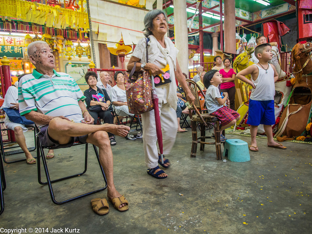 23 SEPTEMBER 2014 - BANGKOK, THAILAND: Spectators watch the Chinese opera on the first day of the Vegetarian Festival at the Chit Sia Ma Chinese shrine in Bangkok. The Vegetarian Festival is celebrated throughout Thailand. It is the Thai version of the The Nine Emperor Gods Festival, a nine-day Taoist celebration beginning on the eve of 9th lunar month of the Chinese calendar. During a period of nine days, those who are participating in the festival dress all in white and abstain from eating meat, poultry, seafood, and dairy products. Vendors and proprietors of restaurants indicate that vegetarian food is for sale by putting a yellow flag out with Thai characters for meatless written on it in red.    PHOTO BY JACK KURTZ