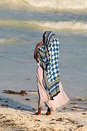 A young girl standing in surf on Paje Beach, Paje, Zanzibar, Tanzania