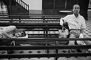 A girl sleeps next to a man inside a church in Trinidad, Cuba. February/2014.