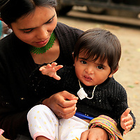 Asia, Bhutan, Wengdue. Young mother feeding her child in Wengdue, Bhutan.
