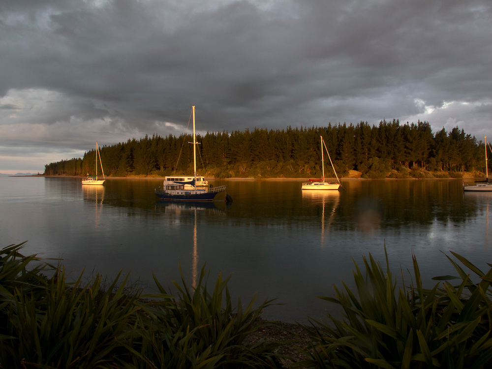 boats at sunset on Mapua wharf Sail boats on Mapua Inlet , Nelson, South Island.