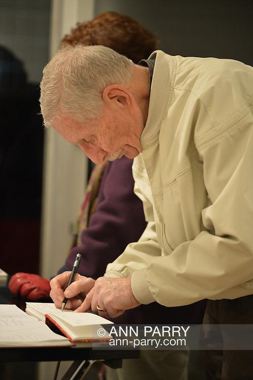 Man signing guest book at Fotofoto Gallery Opening Reception, on November 8, 2014, at Huntington, Long Island, New York, USA