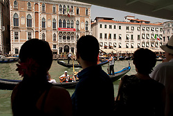 Europe, Italy, Venice, people on vaporetto boat watch gondolas on Grand Canal