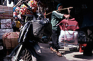 Vietnamese woman carrying bags with her yoke in a street of Hanoi