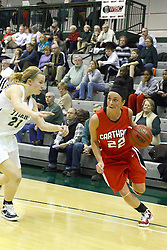 29 January 2011: Heather Gilmore bites her tongue and drives in from the left against Nikki Preston during an NCAA Womens basketball game between the Carthage Reds and the Illinois Wesleyan Titans at Shirk Center in Bloomington Illinois.
