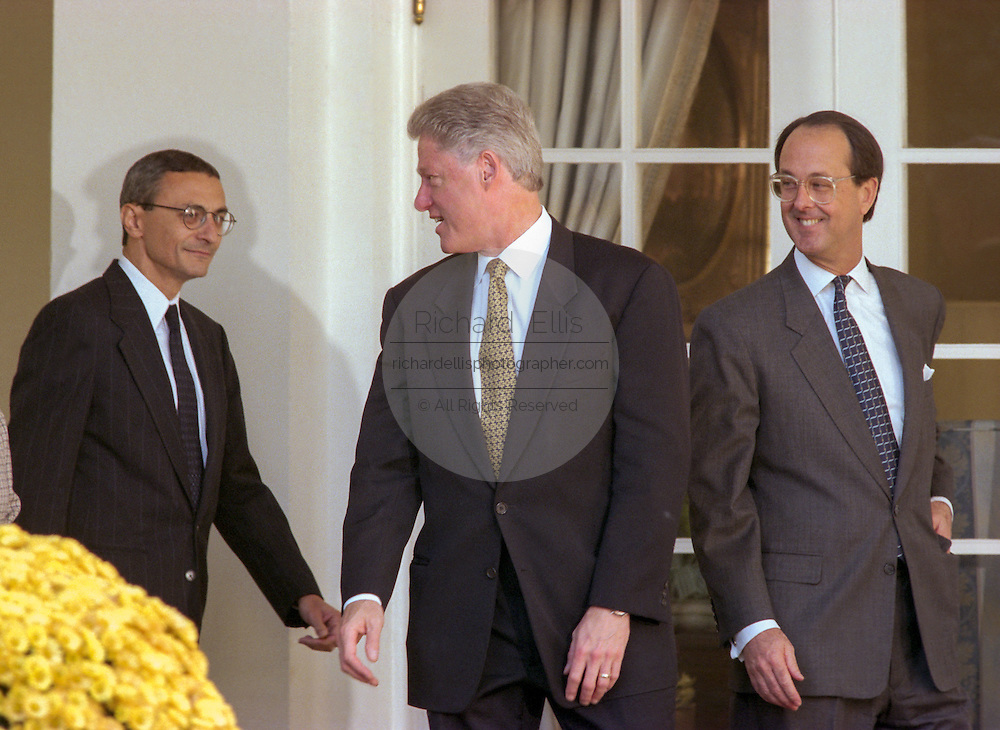 US President Bill Clinton walks with out-going Chief of Staff Erskine Bowles, right, and incoming chief John Podesta, left, from the Oval Office to a Rose Garden ceremony at the White House October 20, 1998 in Washington, DC. Clinton announced John Podesta as the new chief of staff replacing Bowles.