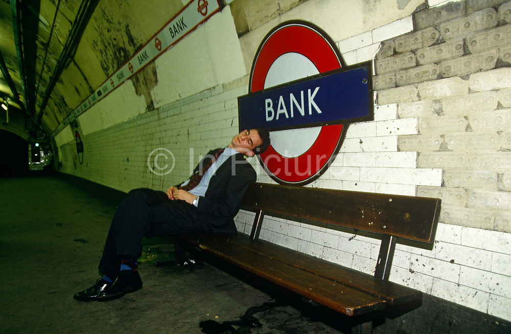 It is late in the City of London, long after offices workers have left their desks in the capital's financial district. But some  commuters like this young man have stayed behind in the Square Mile (the oldest, historic quarter first inhabited by the Romans) to drink with friends. He has consumned so much alcohol that he's passed-out, asleep on a bench on the platform at Bank station, immediately beneath the busy streets at the Bank of England. The station is otherwise deserted and is possibly just before - or after - the last train has left to take others home in the east end or the west.