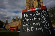 A blackboard listing the latest Ladbrokes betting prices on a Hung Parliament versus a majority voctoary for the Conservative Party in Britain's general election on 6th May 2010. Below the Palace of Westminster, in evening light, the Conservatives appear to be leading while without a majority, pointing to the possibility of a hung Parliament, the first time such a division of power since 1974.