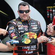 Sprint Cup Series driver Tony Stewart (14) signs autographs for fans during the 57th Annual NASCAR Coke Zero 400 race first practice session at Daytona International Speedway on Friday, July 3, 2015 in Daytona Beach, Florida.  (AP Photo/Alex Menendez)