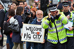© Licensed to London News Pictures.  11/06/2013. LONDON, UK. A protester holds a sign during an anti G8 protest in London ahead of the start of the conference in Northern Ireland. Photo credit: Cliff Hide/LNP