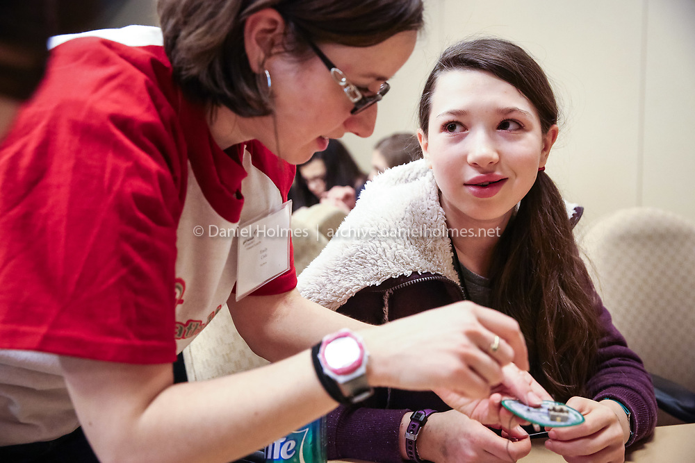(3/9/14, FRAMINGHAM, MA) Instructor Emily Cislo helps eighth-grader Lyndsey Rotman of Duxbury make a battery-powered LED patch during a workshop at the Girl Scouts of Eastern Massachusetts STEM Conference at the Sheraton Hotel in Framingham on Sunday. Over 100 girls between the ages of 11 and 17 attended to gain firsthand experience in science, technology, engineering, and math fields. Daily News and Wicked Local Photo/Dan Holmes