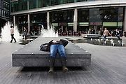 As children play in fountains and pedestrians pass-by, a woman lies across a stone landscaped table in  London's South Bank.