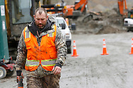A rescue worker carrying a saw leaves the mudslide (right rear) after searching for victims in Oso, Washington March 30, 2014. Local churches offered prayers on Sunday for the victims of last week's devastating mudslide in Washington state and words of solace for grieving families and friends, many of whom are still waiting for news of missing loved ones.  REUTERS/Rick Wilking (UNITED STATES)