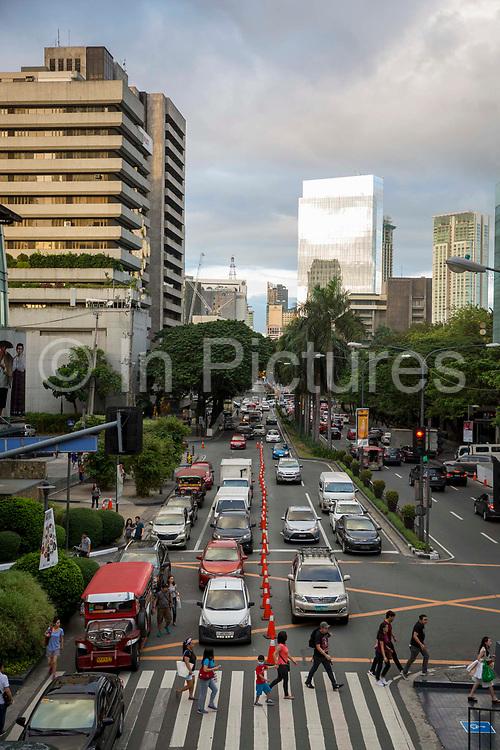 Pedestrians using a zebra crossing to cross Palm Drive in Makati, Metro Manila, Philippines