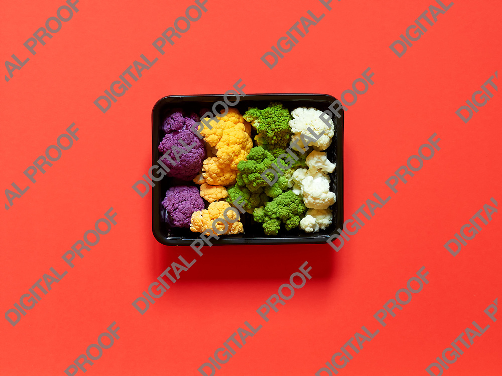 Set of seasonal and colorful cauliflower violet, yellow, green and white boxed in a plastic recipient  over a red background
