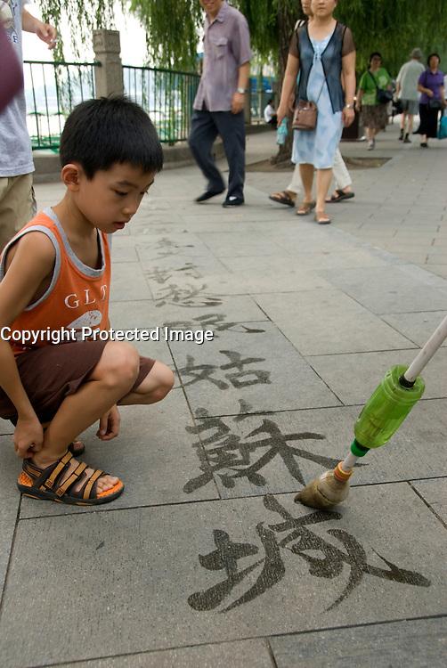 Boy watching Chinese poetry written by brush and water on ground in Beihai Park Beijing