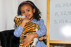 Four-year-old Alannah George gives her favourite toy, a tiger, a cuddle.  She has an IQ of 140 and taught herself to read at two-and-a-half, is a member of Mensa. Iver, Buckinghamshire, March 10 2019.