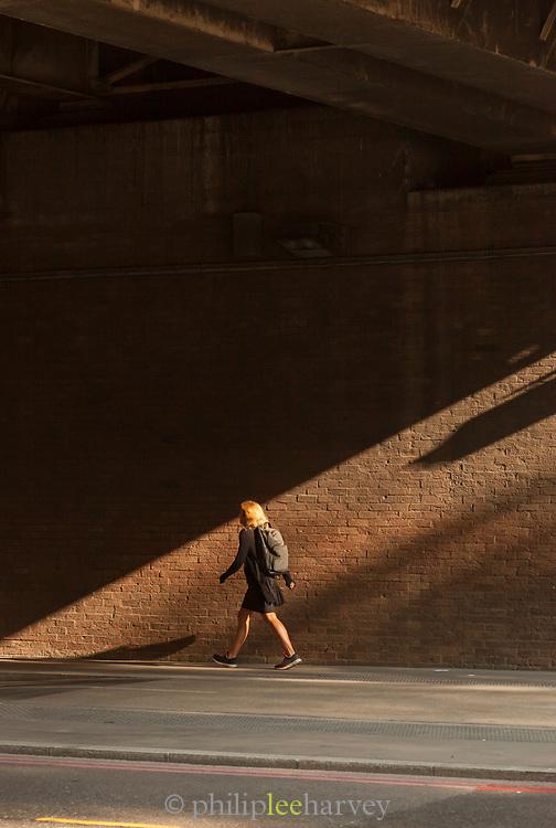 Woman with rucksack walking under bridge, London, England, UK