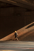 Woman with rucksack walking under bridge, London, England, UK