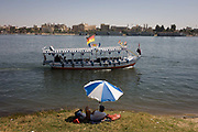 A privately-owned motorboat ferry flying the German flag and dependent on all tourist trade crosses the River Nile in front of a sunbather at Luxor, Nile Valley, Egypt. Plying the great African river is a cheap fare state-run ferry used by commuters and locals but these motorboats serve tourists and therefore one of the many victims of the tourism downturn. According to the country's Ministry of Tourism, European visitors to Egypt is down by up to 80% in 2016 from the suspension of flights after the downing of the Russian airliner in Oct 2015. Euro-tourism accounts for 27% of the total flow and in total, tourism accounts for 11.3% of Egypt's GDP.