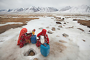 Haji Bootoo Boi's daughters fetching water through a hole in the ice on the frozen river beside Tchelap, one of the claimed source of the Oxus..The Kyrgyz settlement of Tchelab, near Chaqmaqtin lake, Haji Bootoo Boi's camp...Trekking through the high altitude plateau of the Little Pamir mountains, where the Afghan Kyrgyz community live all year, on the borders of China, Tajikistan and Pakistan.