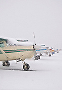 Alaska. Anchorage. Merrill Field. Snowy aircraft line-up. Snow limits visibility and grounds most small planes for the day. Merrill Field is the busiest general aviation airport in the world.