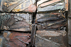 Baled brass and copper car radiators from dismantled vehicles at a metal recycling centre,