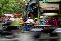 Flower seller moves amongst all the hustle and bustle of Hanoi's old quarter.