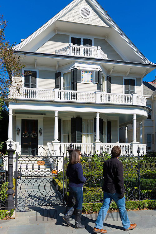 Tourists tour grand mansion houses in the Garden District of New Orleans, Louisiana, USA