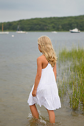 blonde girl walking into the bay at Northwest Harbor in East Hampton