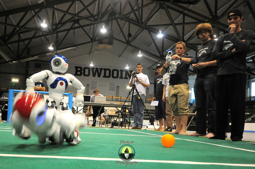 """May 2, 2009 -- BRUNSWICK, Maine. The """"Northern Bites """" team watches closely as their Nao humanoid robot battles for the ball with a competing robot from The University of Texas. Bowdoin hosted the  2009 RoboCup U.S. Open this weekend. Competitors were tasked with creating software for two-legged robots which could independently play soccer with each other. """"Once we put them on the field, they are completely autonomous,""""  said Bowdoin Professor of Computer Science and """"Northern Bites"""" team advisor, Eric Chown said. """"I'm extremely proud of every one on this team. They are competing against teams with students from multiple institutes and graduate students as well. They are a talented and hard-working group!"""" Northern Bites finished fourth out of four teams participating due to injuries to the robots in early play. Photo by Roger S. Duncan."""