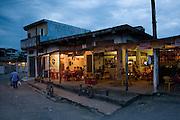 A man takes his shopping home next to a bar  in vila dos pescadores favela, Cubatão
