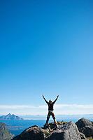 Hiker stands in celebration on summit of Justadtind, Lofoten islands, Norway
