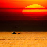A large sun sets on on a boat Raritan Bay (aka New York Harbor or Sandy Hook Bay) looking west from Sandy Hook National Park New Jersey