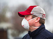 "11 APRIL 2020 - DES MOINES, IOWA: JASON CLARK , from Midwest Foods, directs traffic during a food distribution in Des Moines. Most non-essential businesses in Iowa are closed until 30 April. Because of business closings causes by the Novel Coronavirus (SARS-CoV-2) pandemic, well over 100,000 Iowans filed first time claims for unemployment in the last three weeks, more than applied during the peak of the Great Recession of 2008. Local food banks have seen an unprecedented spike in people seeking nutritional assistance. Midwest Foods, a Des Moines based company and owner of Ginos Fine Italian Foods, gave away 1,000 complete dinners with sauce, noodles, salad, and dressing Saturday morning. People started lining up 3 hours before the food distribution began. The food distribution was done following ""social distancing"" guidelines and all of the workers wore masks and gloves.       PHOTO BY JACK KURTZ"