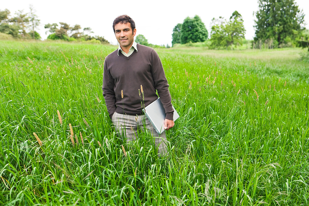 A late 30's early 40's mixed ethnicity (spanish french hispanic italian) businessman standing in a field of high grass holding his laptop computer...Model Release: 20080602_MR_A