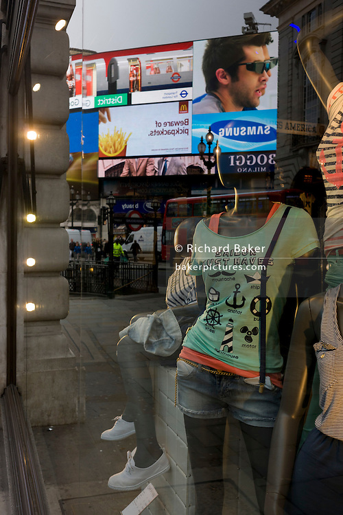 Womens' clothes being modelled on mannequins seen in a window in Picadilly Circus, with advertising reflected behind.