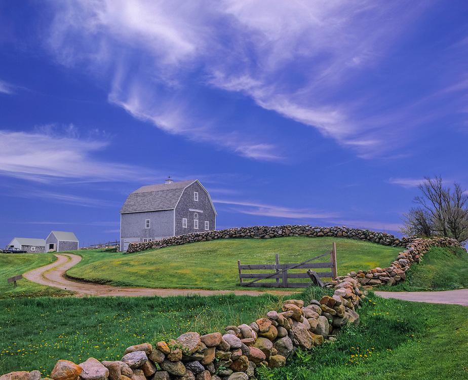 Gambrel barn in spring with lawn, stonewall, driveway & clouds, Block Island, RI