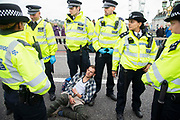 A man is detained by police on Westminster Bridge on 7th October, 2019 in London, Untited Kingdom. Extinction Rebellion plan to occupy 12 sites situated around key Government locations around Westminster for two weeks to protest against climate change.