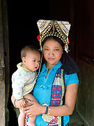 Portrait of an Akha Nuquie woman and her baby in Ban Phanghok, Phongsaly province, Lao PDR. One of the most ethnically diverse countries in Southeast Asia, Laos has 49 officially recognised ethnic groups although there are many more self-identified and sub groups. These groups are distinguished by their own customs, beliefs and rituals. Details down to the embroidery on a shirt, the colour of the trim and the type of skirt all help signify the wearer's ethnic and clan affiliations.