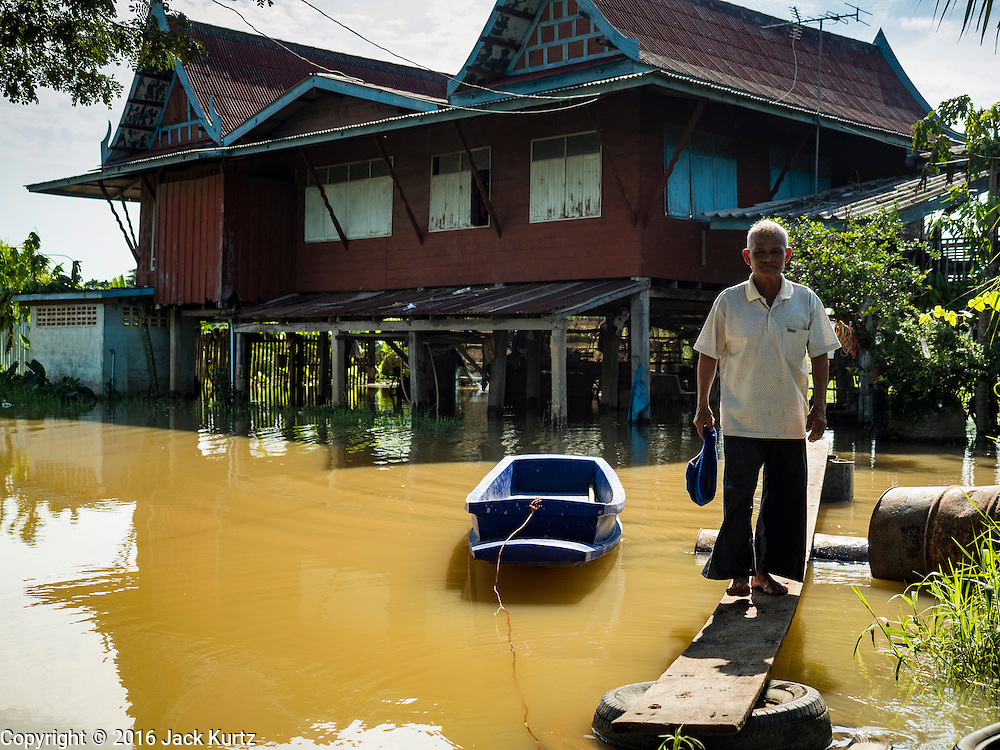 30 SEPTEMBER 2016 - SAI NOI, AYUTTHAYA, THAILAND:  A man leaves his flooded home in Sai Noi. The Chao Phraya River, the largest river that runs through central Thailand, has hit flood stage in several areas in Ayutthaya and Ang Thong provinces. Villages along the river are flooded and farms are losing their crops due to the flood. This is the same area that was devastated by floods in 2011, but the floods this year are not expected to be as severe. The floods are being fed by water released from upstream dams. The water is being released to make room for heavy rains expected in October.     PHOTO BY JACK KURTZ