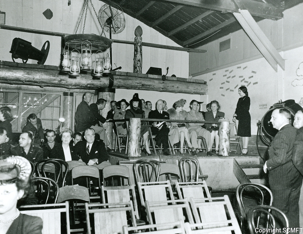 1943 Guest seating area at the Hollywood Canteen during the first anniversary party. Mary Ford, chairman of the kitchen, is wearing a black dress and standing at the right of the seated guest.